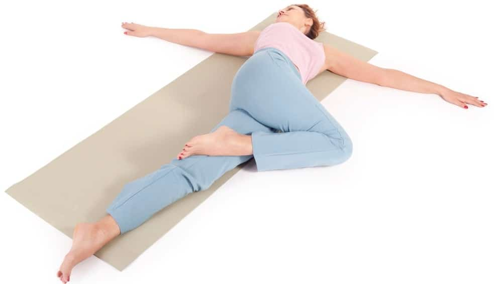 A woman doing the supine spinal twist stretching pose.