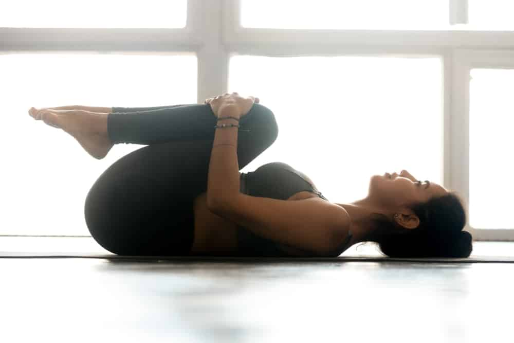 A woman doing the knees to chest stretch exercise.