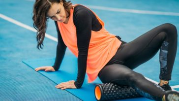 A female athlete stretching her leg with a foam roller.