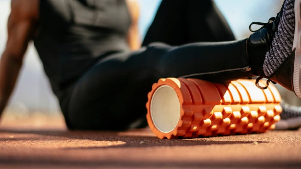 A close look at an athlete using a foam roller to stretch his leg.