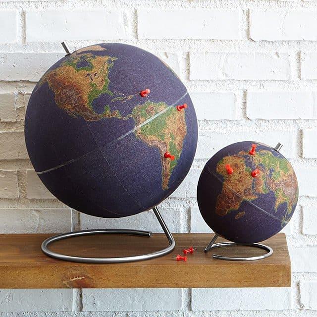 World traveler's cork globes on a floating shelf.