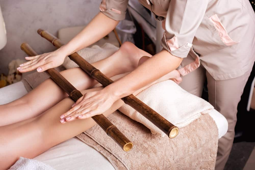 A woman being massaged with the use of massage sticks.