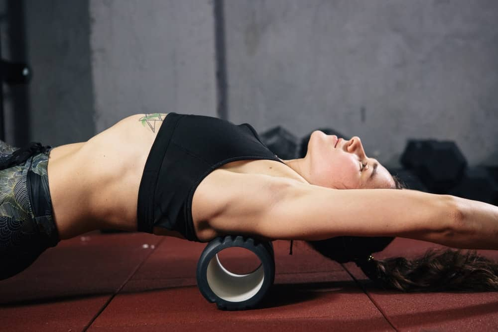 A woman stretching her back with the foam roller.