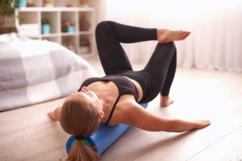A woman exercising at home with a foam roller.
