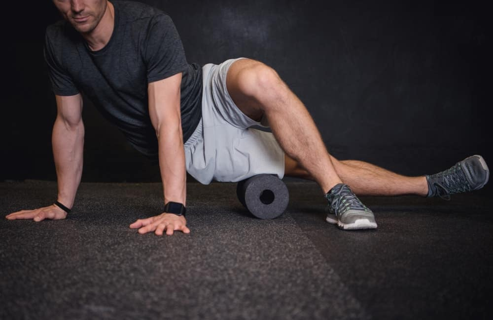 A man exercising with the use of a foam roller.