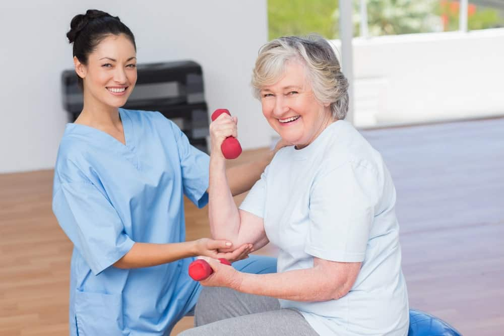 Female therapist assisting senior woman in lifting dumbbells at gym.