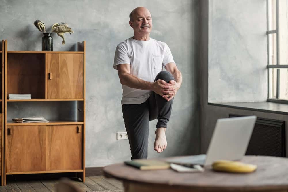 A healthy old man stretching his leg in his living room.