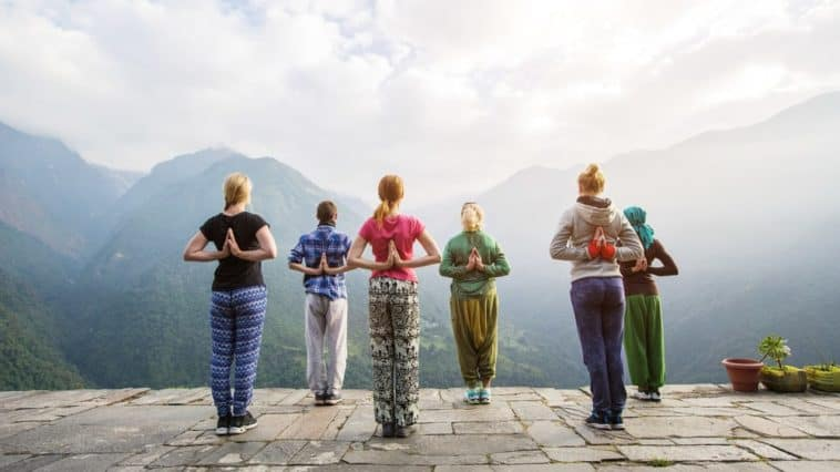 A group of people doing a yoga pose in front of the sweeping mountain view.