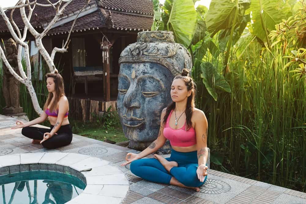 A couple of women meditating at a yoga retreat.