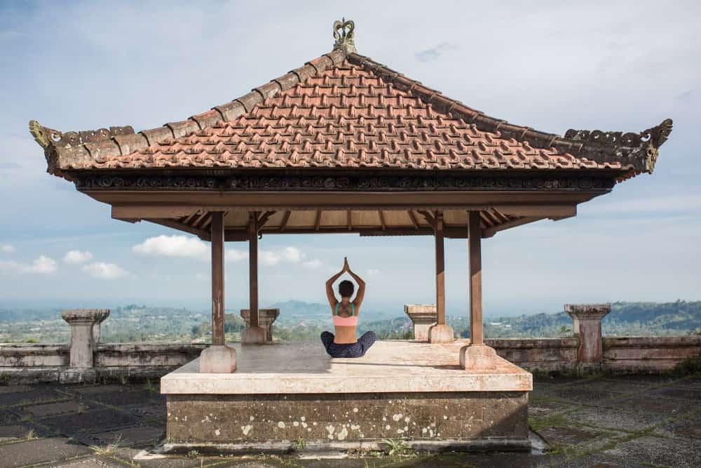 A woman doing yoga at a traditional Balinese gazebo.