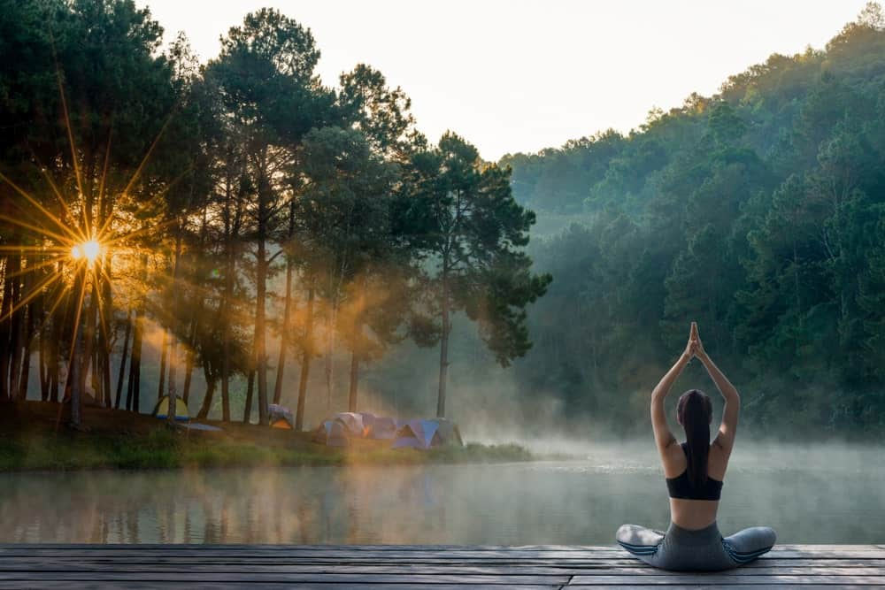 A woman doing a yoga pose while facing a river scenery.