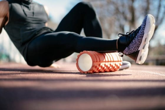 An athlete using a foam roller to stretch his legs.