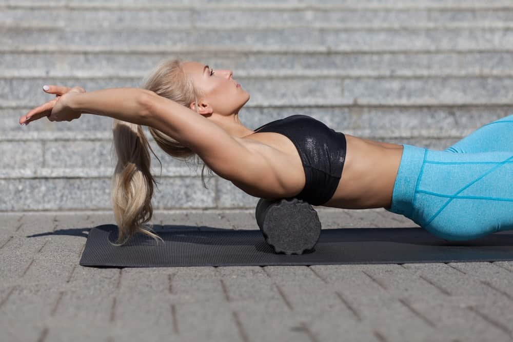 An athlete using a foam roller to stretch her back.