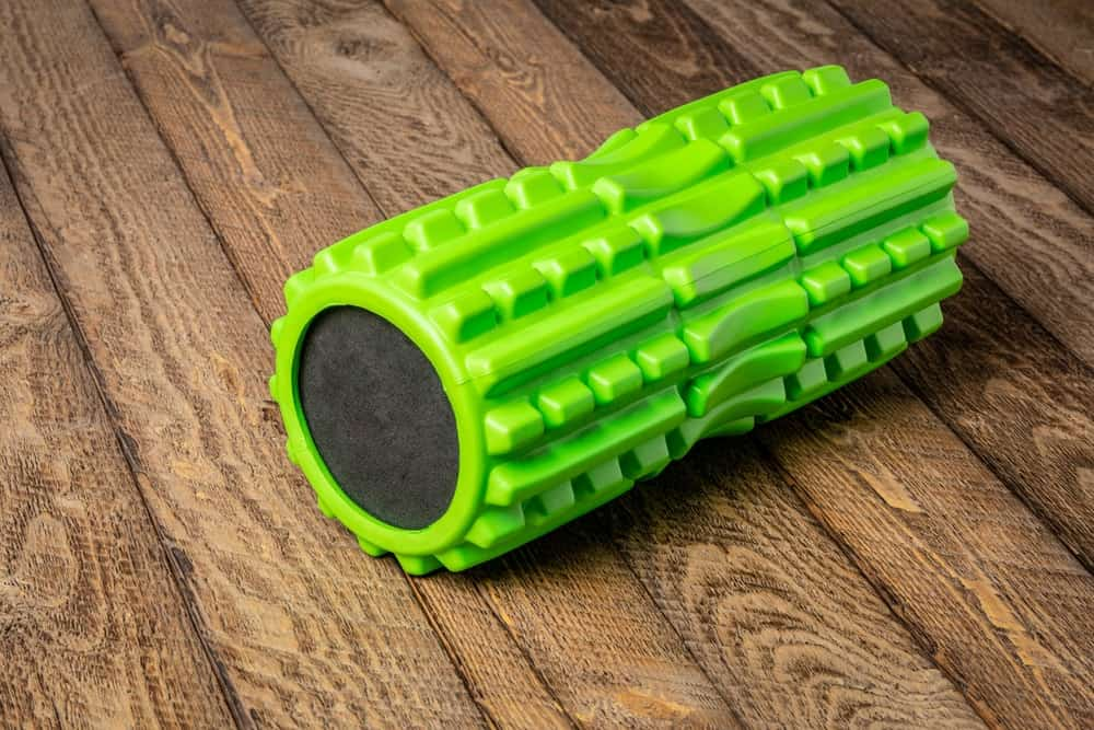 A neon green foam roller with deep tissue massage capabilities on a wooden floor.