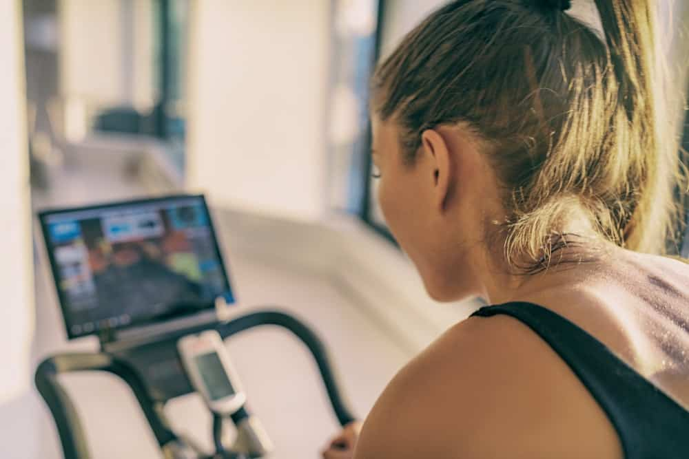 A woman exercising on a stationary bike at home.