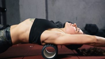 A woman exercises with the use of a hollow foam roller.