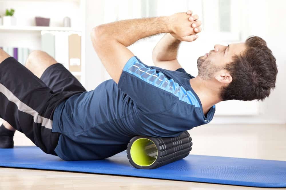 A man exercises his core muscles with the use of a hollow roam roller.