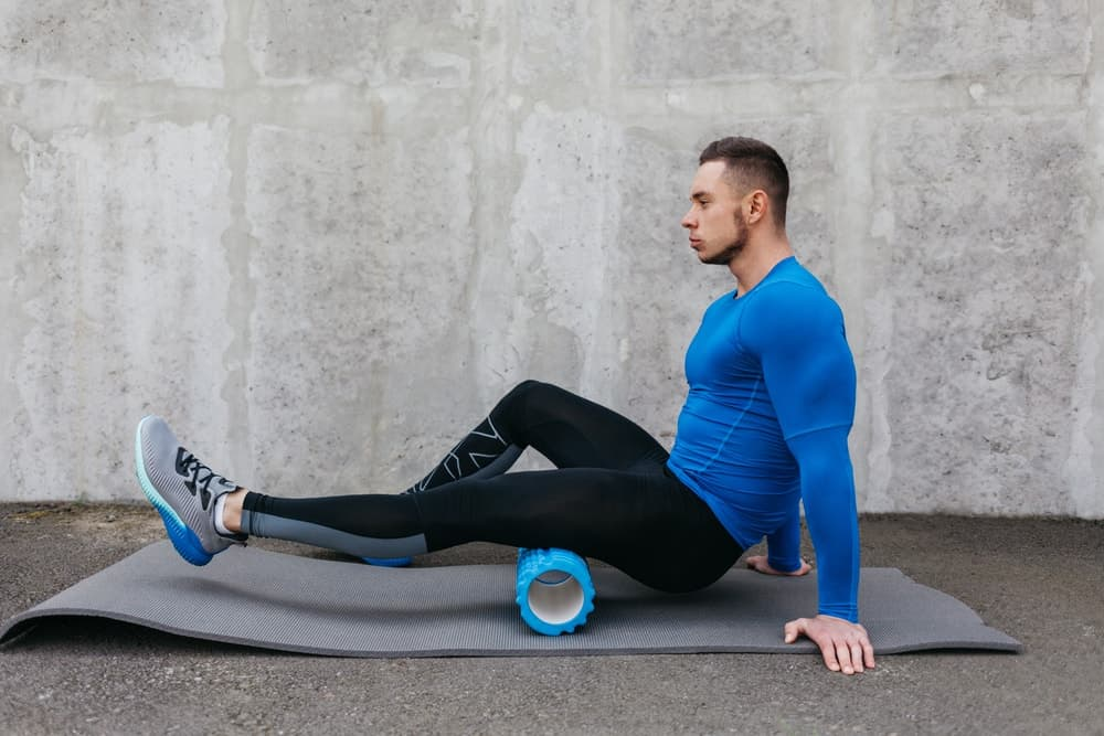 A man stretches his thigh muscles with a hollow foam roller.