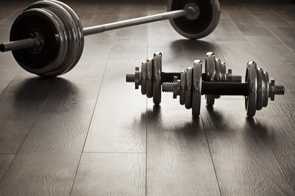 A set of dumbells on the floor with a barbell.