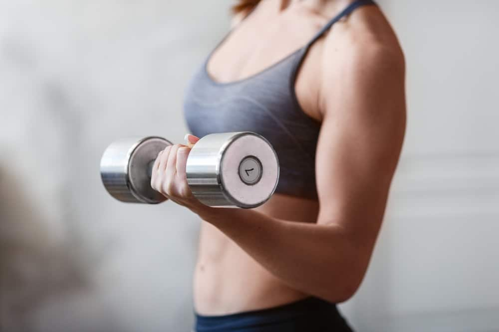 A woman exercising with a dumbell.