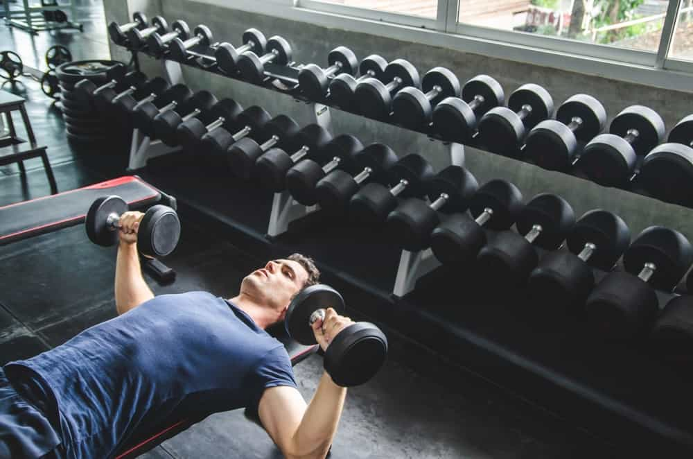 A man exercising in the gym with a couple of dumbells.
