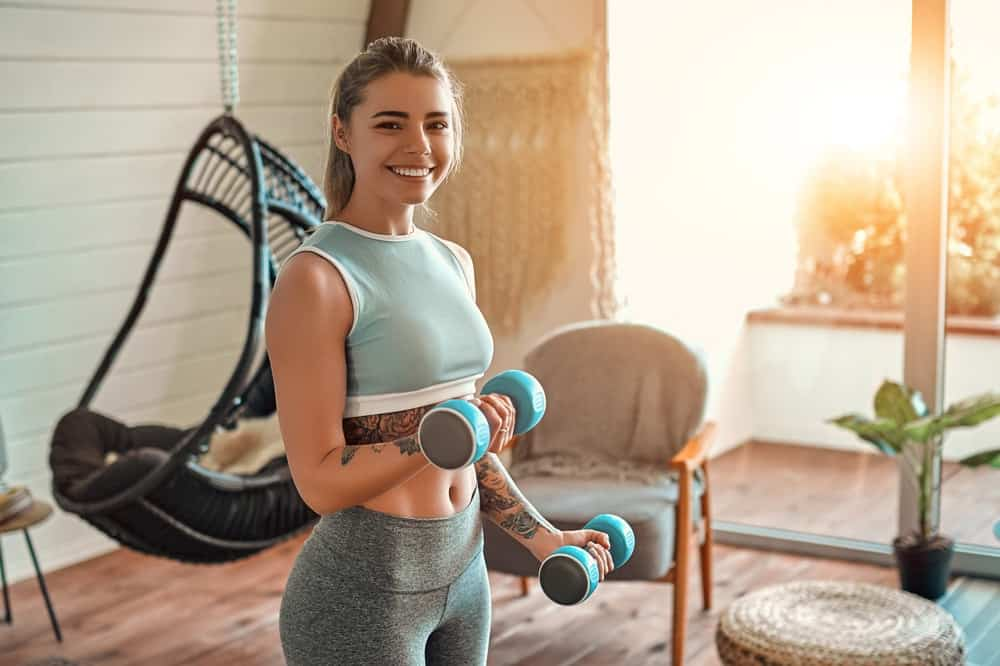 A woman exercising with dumbells at home.