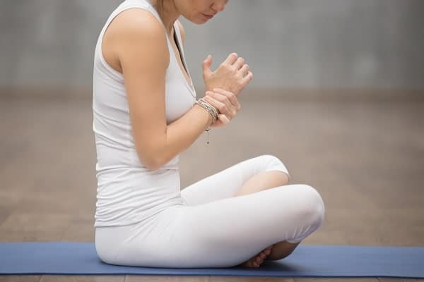 A woman experiencing wrist pain while doing yoga.
