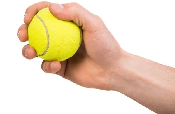 A close look at the hand of a man squeezing a tennis ball.