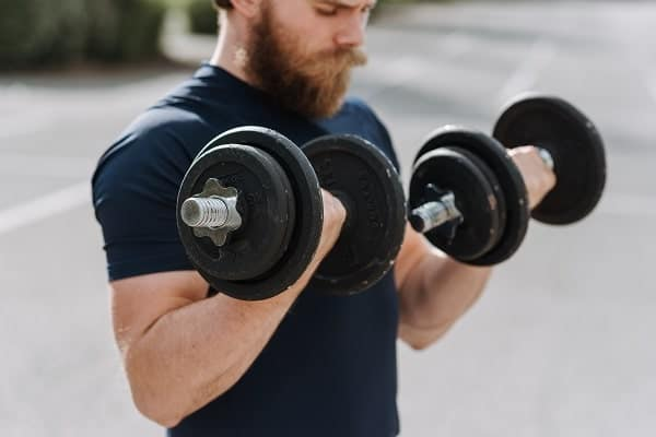 A man doing bicep curls with dumbells from Pexels.
