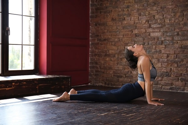 A woman practicing a yoga pose indoors.