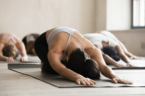 A woman on a yoga mat practicing a yoga pose along with a group of people indoors.