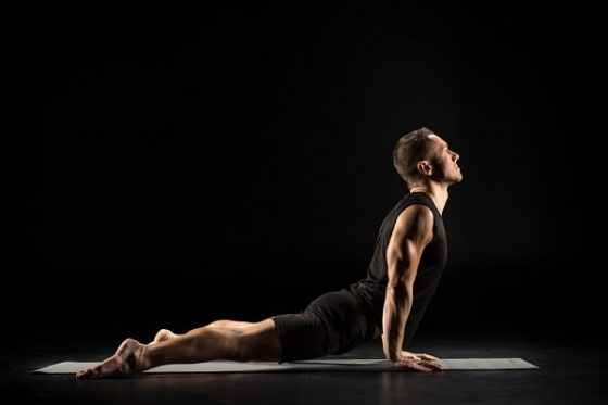 A man in a tank top and yoga shorts practicing yoga on a mat inside a studio.