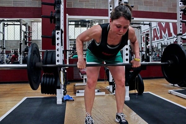 A woman doing a barbell row exercise at an indoor gym from Wikimedia Commons.