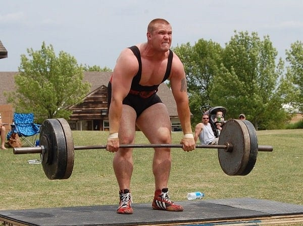A weightlifter doing phase 2 of a deadlift at an open field from Wikimedia Commons.