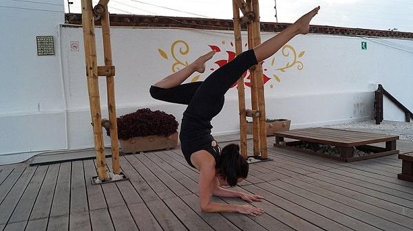 A woman doing the Pincha Mayurasana yoga pose on a wooden floor from Wikimedia Commons.