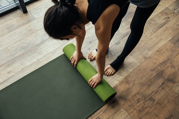 A woman putting a yoga mat on the wooden floor.