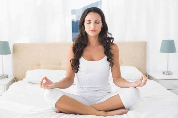 A woman doing a yoga pose on the bed.