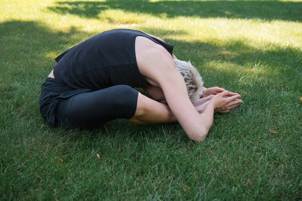 A woman doing a yoga pose on a grassy lawn.