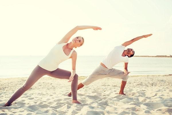 A couple doing their yoga pose on a sandy beach.