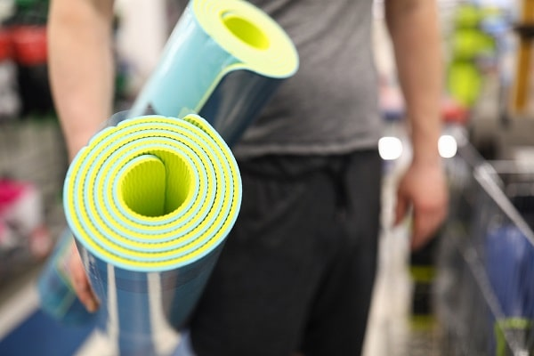 A man holding two yoga mats at a store.