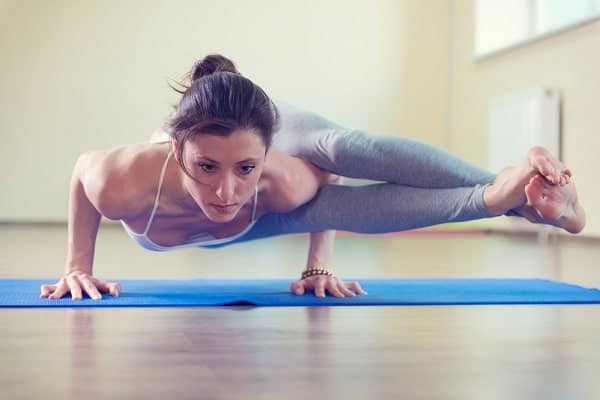 A woman doing a strength training yoga pose on a blue mat in an indoor studio.