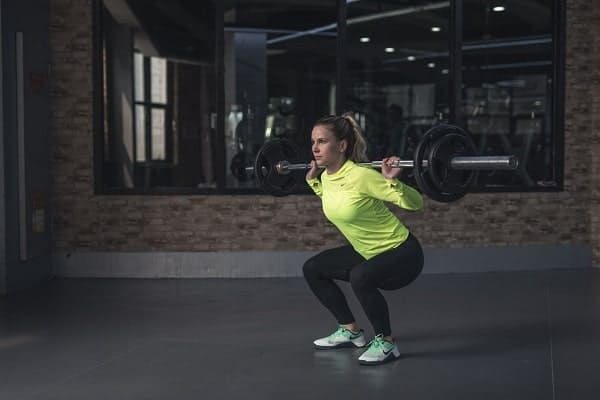 A woman lifting a barbell in a weightlifting studio from Pexels.