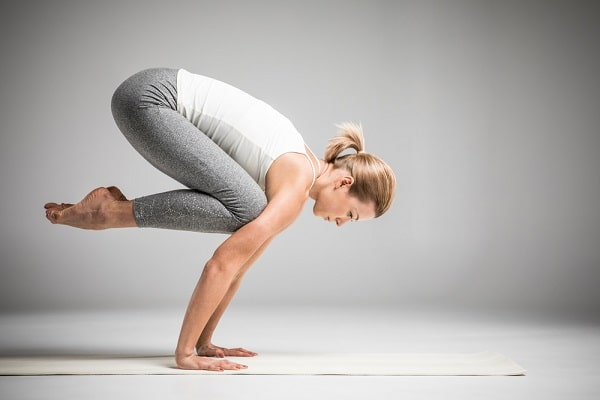 A woman standing on the floor in a challenging yoga position.