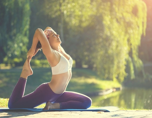 A woman doing a yoga pose at a park in the morning.