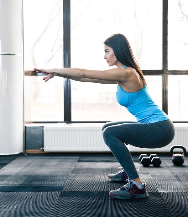 A woman doing squats at an indoor gym.
