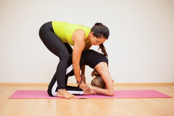 A female yoga teacher demonstrating to a student how she can achieve a difficult yoga pose correctly.