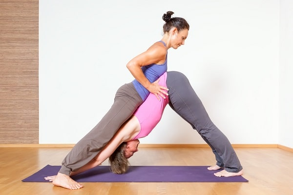 A female yoga instructor helping a student achieve a difficult pose.