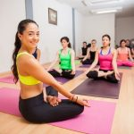 A yoga instructor smiling while her class is doing a meditative yoga pose.