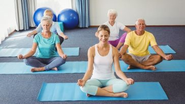 A yoga instructor leading a yoga class for seniors during a meditative pose.