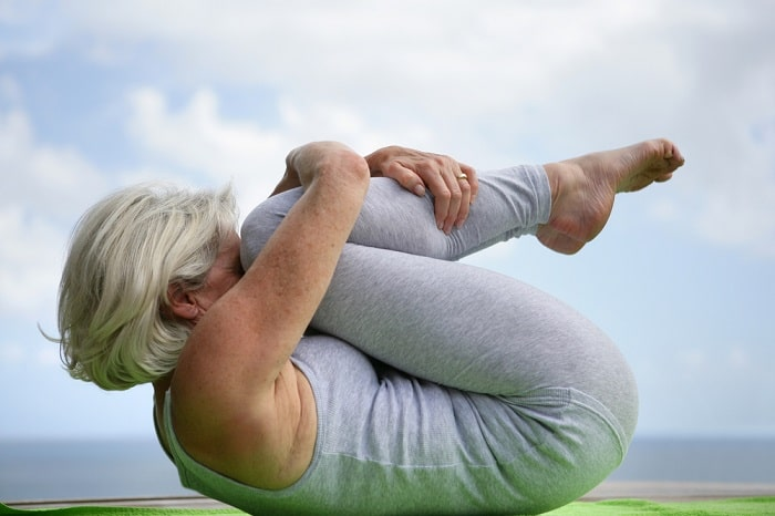 A senior woman demonstrating flexibility during a challenging yoga pose.